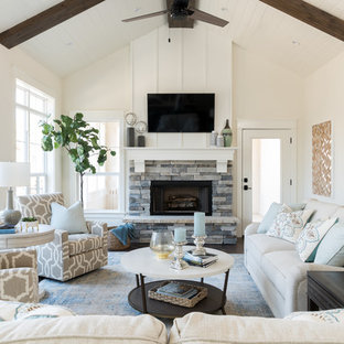 This is an example of a medium sized coastal family and games room with white walls, a standard fireplace, a stone fireplace surround, a wall mounted tv and dark hardwood flooring.