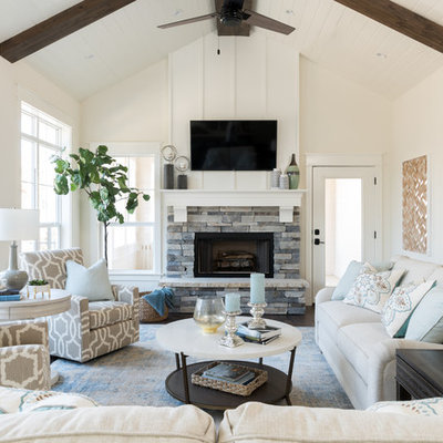 Mid-sized beach style dark wood floor family room photo with white walls, a standard fireplace, a stone fireplace and a wall-mounted tv