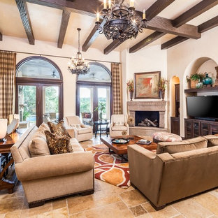 Example of a large tuscan open concept beige floor and travertine floor family room design in Houston with beige walls, a corner fireplace and a tv stand
