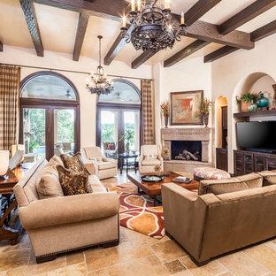 Großes, Offenes Mediterranes Wohnzimmer mit beiger Wandfarbe, Eckkamin, beigem Boden, Travertin und freistehendem TV in Houston