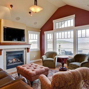 Foto di un soggiorno chic con pareti rosse, pavimento in legno massello medio, camino classico e TV a parete