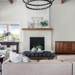 Großes, Fernseherloses, Offenes Maritimes Wohnzimmer mit grauer Wandfarbe, braunem Holzboden, Kamin, Kaminumrandung aus Holzdielen, braunem Boden und freigelegten Dachbalken in Austin