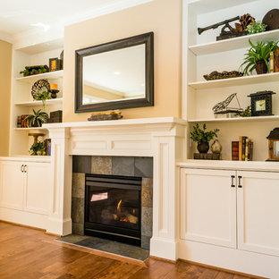ポートランドの大きいトラディショナルスタイルのおしゃれなファミリールーム (無垢フローリング、標準型暖炉、タイルの暖炉まわり、壁掛け型テレビ、ベージュの壁、茶色い床) の写真