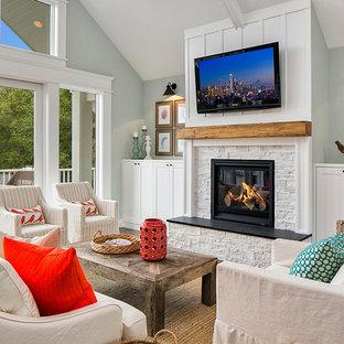 シアトルのビーチスタイルのおしゃれなファミリールーム (青い壁、標準型暖炉、石材の暖炉まわり、壁掛け型テレビ) の写真