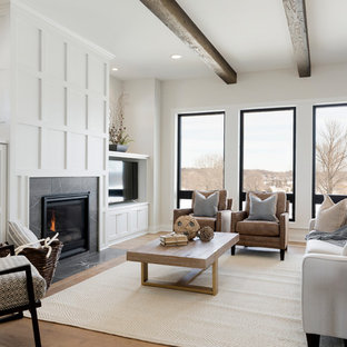 This is an example of a rural family and games room in Minneapolis with white walls, medium hardwood flooring, a standard fireplace, a tiled fireplace surround, a wall mounted tv and brown floors.