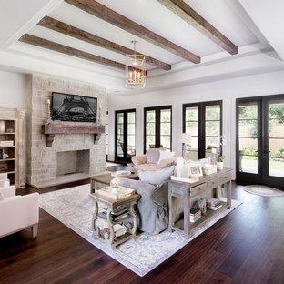 ヒューストンの巨大なトラディショナルスタイルのおしゃれなファミリールーム (白い壁、濃色無垢フローリング、標準型暖炉、石材の暖炉まわり、壁掛け型テレビ、茶色い床、ライブラリー) の写真
