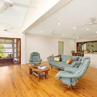 Exemple d'une salle de séjour exotique de taille moyenne et ouverte avec un mur beige, un sol en bois clair, un téléviseur indépendant et un sol marron.