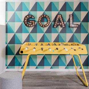 Ejemplo de sala de juegos en casa abierta, contemporánea, pequeña, sin chimenea, con suelo de baldosas de cerámica, televisor colgado en la pared, suelo gris y paredes multicolor