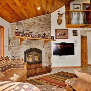 他の地域の広いラスティックスタイルのおしゃれなオープンリビング (白い壁、セラミックタイルの床、薪ストーブ、石材の暖炉まわり、壁掛け型テレビ、ベージュの床) の写真
