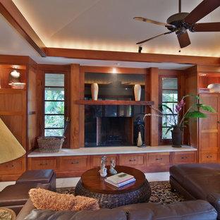 サンディエゴの中サイズのトロピカルスタイルのおしゃれなファミリールーム (ベージュの壁、トラバーチンの床、標準型暖炉、石材の暖炉まわり、内蔵型テレビ) の写真