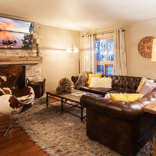 Immagine di un soggiorno rustico aperto con pareti marroni, pavimento in legno massello medio, camino classico, cornice del camino in pietra e TV a parete