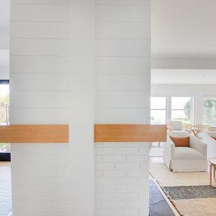Неиссякаемый источник вдохновения для домашнего уюта: большая открытая гостиная комната в морском стиле с белыми стенами, светлым паркетным полом, двусторонним камином, фасадом камина из вагонки и телевизором на стене