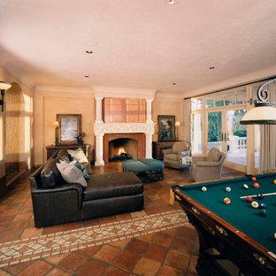 シアトルの中サイズの地中海スタイルのおしゃれな独立型ファミリールーム (ゲームルーム、ベージュの壁、テラコッタタイルの床、標準型暖炉、石材の暖炉まわり、内蔵型テレビ) の写真
