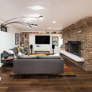 Foto de sala de estar con biblioteca cerrada, vintage, de tamaño medio, con paredes blancas, suelo de madera oscura, chimenea tradicional, marco de chimenea de ladrillo, televisor colgado en la pared y suelo marrón