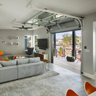 Foto de sala de estar abierta, contemporánea, pequeña, sin chimenea, con paredes grises, suelo de cemento, televisor colgado en la pared y suelo gris