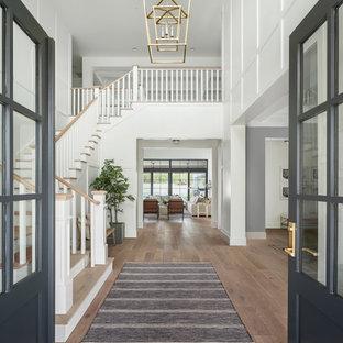 Esempio di un grande soggiorno country stile loft con sala giochi, pareti bianche, parquet chiaro, camino classico, cornice del camino in mattoni, TV a parete e pavimento beige