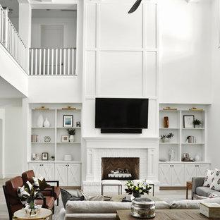 Foto de sala de juegos en casa tipo loft, campestre, grande, con paredes blancas, suelo de madera clara, chimenea tradicional, marco de chimenea de ladrillo, televisor colgado en la pared y suelo beige