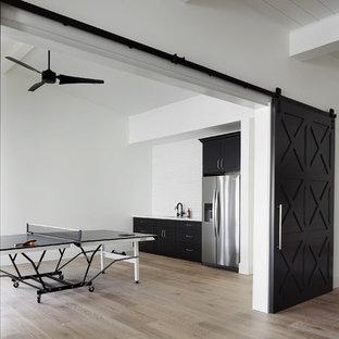 Foto på ett stort lantligt allrum på loftet, med ett spelrum, vita väggar, ljust trägolv, en standard öppen spis, en spiselkrans i tegelsten, en väggmonterad TV och beiget golv