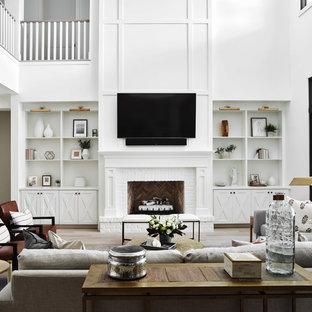 Idéer för stora lantliga allrum med öppen planlösning, med vita väggar, ljust trägolv, en standard öppen spis, en spiselkrans i tegelsten, en väggmonterad TV och beiget golv