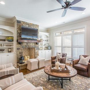 Idées déco pour une salle de séjour classique avec un mur blanc, un sol en bois brun, une cheminée standard, un manteau de cheminée en pierre, un téléviseur fixé au mur et un sol marron.