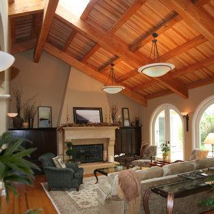 サンフランシスコの中サイズのトラディショナルスタイルのおしゃれなファミリールーム (ベージュの壁、淡色無垢フローリング、標準型暖炉、漆喰の暖炉まわり、ベージュの床) の写真