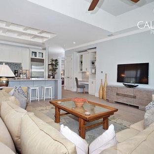 Idée de décoration pour une salle de séjour ethnique ouverte avec un sol en bois clair et un téléviseur fixé au mur.