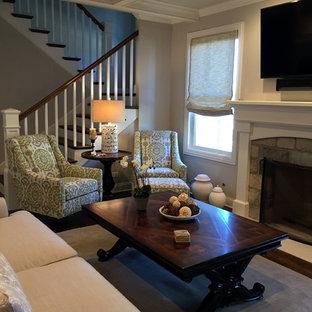 Immagine di un soggiorno contemporaneo di medie dimensioni e chiuso con pareti grigie, parquet scuro, camino classico, cornice del camino in pietra, TV a parete e pavimento verde