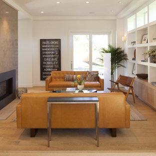 Foto di un soggiorno minimalista con pareti bianche, pavimento in legno massello medio, camino classico e nessuna TV
