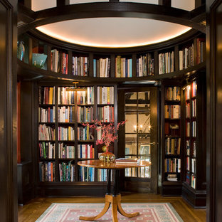 Large elegant enclosed dark wood floor and brown floor family room library photo in New York