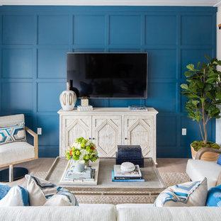 オレンジカウンティのビーチスタイルのおしゃれなファミリールーム (青い壁、淡色無垢フローリング、壁掛け型テレビ) の写真