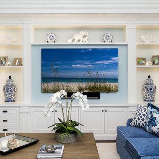 マイアミの大きいビーチスタイルのおしゃれなファミリールーム (青い壁、濃色無垢フローリング、暖炉なし、埋込式メディアウォール) の写真