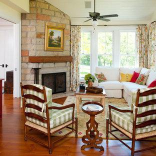 Cette photo montre une grand salle de séjour nature ouverte avec un sol en bois brun, une cheminée d'angle et un manteau de cheminée en pierre.