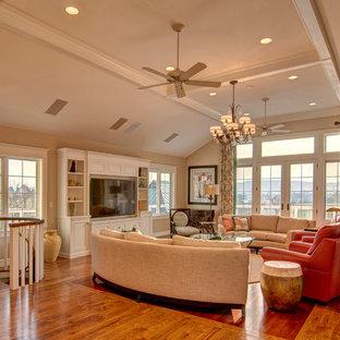 Immagine di un soggiorno chic con pareti beige, pavimento in legno massello medio e parete attrezzata