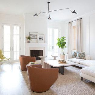 Diseño de sala de estar con biblioteca abierta, moderna, extra grande, con paredes blancas, suelo de madera clara, chimenea tradicional, marco de chimenea de piedra y televisor colgado en la pared