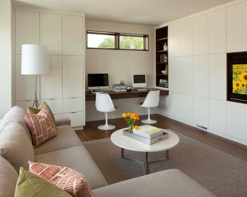 minimalist family room photo in minneapolis with beige walls dark hardwood floors and a built - Built In Desk Designs