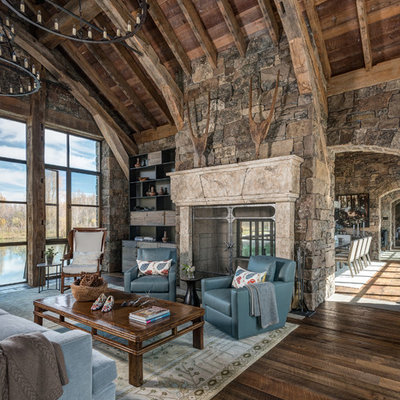 Large mountain style open concept dark wood floor family room library photo in Jackson with a two-sided fireplace, a stone fireplace, no tv and beige walls