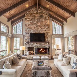 Идея дизайна: большая открытая гостиная комната в стиле рустика с фасадом камина из камня, белыми стенами, стандартным камином и телевизором на стене