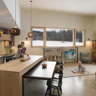 Modelo de sala de estar abierta, contemporánea, pequeña, con paredes beige, suelo de cemento, estufa de leña y marco de chimenea de baldosas y/o azulejos
