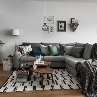 Family room - scandinavian open concept medium tone wood floor and brown floor family room idea in San Francisco with white walls and a tv stand