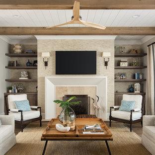 Ejemplo de sala de estar cerrada, marinera, con paredes grises, suelo de madera oscura, chimenea tradicional, televisor colgado en la pared y suelo marrón