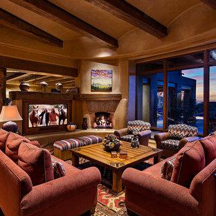 フェニックスの大きいサンタフェスタイルのおしゃれなファミリールーム (ベージュの壁、淡色無垢フローリング、標準型暖炉、漆喰の暖炉まわり、埋込式メディアウォール) の写真