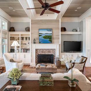 Idee per un grande soggiorno tradizionale aperto con pareti grigie, pavimento in legno massello medio, camino classico, cornice del camino in mattoni e parete attrezzata