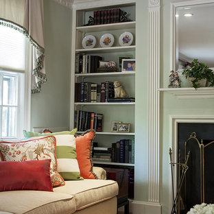 Diseño de sala de estar cerrada, ecléctica, pequeña, con paredes verdes, suelo de madera en tonos medios, chimenea tradicional, marco de chimenea de piedra, televisor retractable y suelo beige