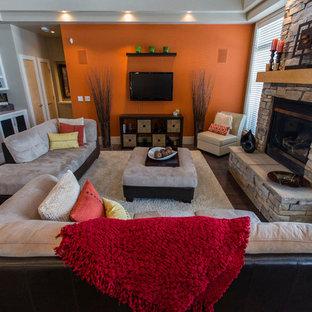 Idées déco pour une grande salle de séjour avec un mur orange, un sol en bois foncé, une cheminée standard, un manteau de cheminée en pierre et un téléviseur fixé au mur.