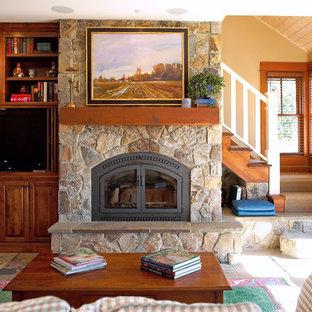 Réalisation d'une salle de séjour champêtre avec un mur jaune, un sol en ardoise, une cheminée standard, un manteau de cheminée en pierre et un téléviseur encastré.