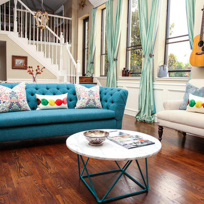 Example of a mid-sized eclectic medium tone wood floor family room design in Houston with beige walls