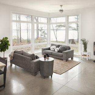 Cette image montre une salle de séjour design ouverte avec béton au sol, un mur gris, un poêle à bois et un sol gris.