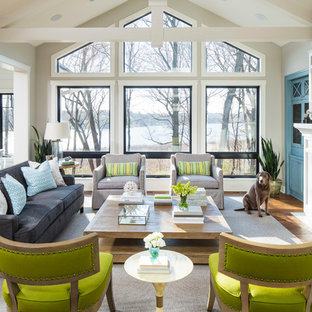 Inspiration for a beach style open concept medium tone wood floor family room remodel in Minneapolis with gray walls, a standard fireplace, a wall-mounted tv and a tile fireplace