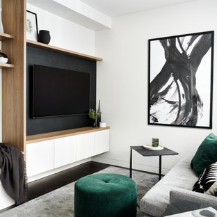 Small scandinavian open concept family room in Sydney with white walls, dark hardwood floors, a built-in media wall and brown floor.