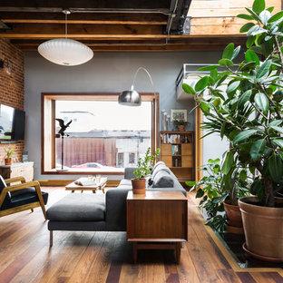 ニューヨークの中サイズのインダストリアルスタイルのおしゃれなオープンリビング (無垢フローリング、薪ストーブ、グレーの壁) の写真
